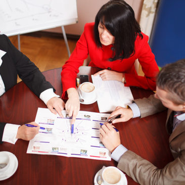 High angle view of a dedicated business team of two women and a man seated at a table having a meeting brainstorming a new project and analysing a document